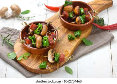 Spanish snack: Pincho skewers with fried chorizo sausage, pimentos de padron and mushrooms