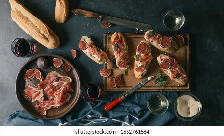 Spanish snacks and wine on a dark concrete background. tapas, pinchos, bruschetta of Delicious ham, jamon, baguette, figs, cheese and herbs on the dining table.