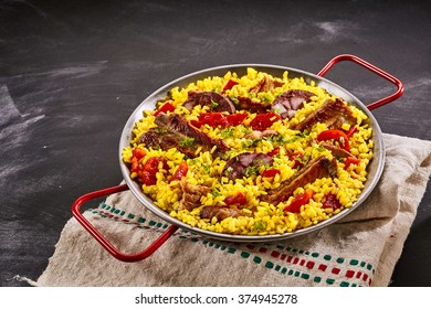 Spanish speciality paella al homo with spare ribs and black pudding on a bed of yellow saffron rice, herbs and red bell pepper served in a metal pan over slate with copy space