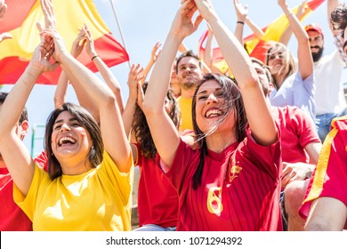 Spanish supporters cheering clapping hands at stadium. Group of fans watching a match and cheering team Spain with flags and chants. Sport and lifestyle concepts.