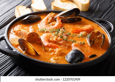 Spanish Suquet de Peix sea soup with potatoes, shrimps, mussels, herbs and fish with picada in a pan on the table. horizontal
