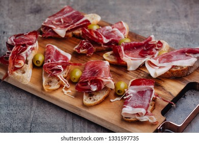 Spanish tapas with ham and olives on cutting board