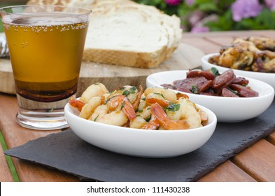 Spanish Tapas - Hot & Spicy Spanish appetisers. (pollo al ajillo, gambas pil pil and chorizo al vino). Served with Mediterranean bread and beer.