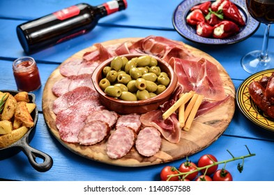 Spanish tapas and red wine on black table, top view