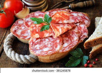 Spanish tapas - sliced salame on rustic wooden cutting board with bread and tomatoes