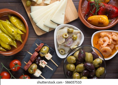 Spanish tapas starters on old wooden table. Top view