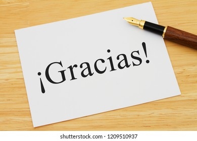 Spanish thank you message, A white card on a desk with a pen with text Gracias