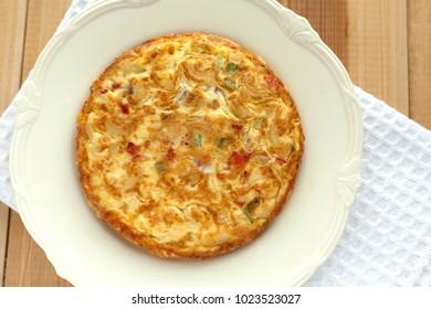 Spanish tortilla on white dish.