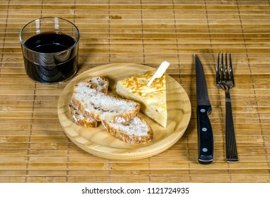 Spanish tortilla skewer presented in typical ration of Spain, With bread and a glass of red wine