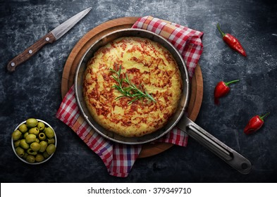 Spanish tortilla with vegetables and herbs on frying pan on blac