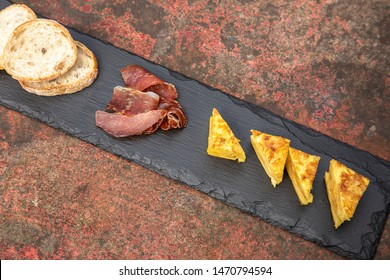 Spanish traditional Tortilla ham jamon and bread on a rusty tabl