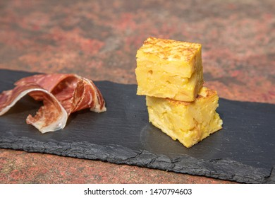 Spanish traditional Tortilla ham jamon on a rusty table