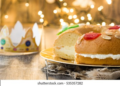 "Spanish typical epiphany cake ""Roscon de Reyes"", and christmas light on wooden background"