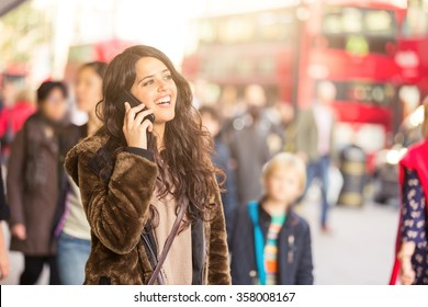 Spanish woman talking on the phone with blurred people on background in a busy street of London. She is wearing a fur and looking away from camera. Lifestyle and travel concepts.