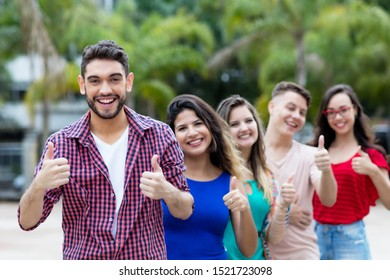 Spanish young adult hipster man with group of friends in line outdoor in the city in summer