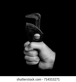 spanner - tools in a man's hand on black background - black and white photo