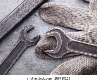 Spanners and gloves on a metal background