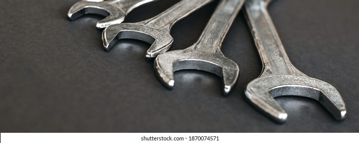 Spanners. Many wrenches. Grey background. Set of wrenches in different sizes on grey background.Close up. Blurred background.