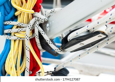 Spare multi-colored ropes tied to the mast of a sailing ship, close-up. One rope is fixed on the fixing rollers on the sailboat mast.