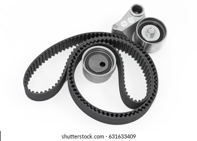 Spare parts for the ca r. Kit of timing belt with rollers on a light background.