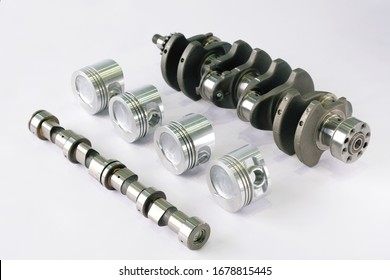 Spare parts for the car engine. Crankshaft with sprocket Assembly, camshaft and pistons complete on white background, top view.