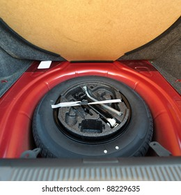Spare tire in the trunk of a red modern car. Useful photograph for our repair brochure, auto service  advertising or flyer.
