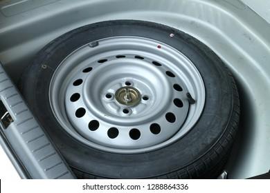 Spare wheel in storage bin on a car