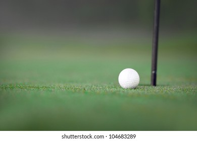 Spares image with golf ball on green near hole