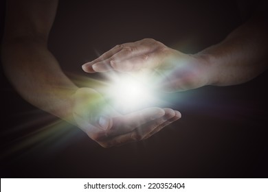 The Spark of Life - Male hands emerging from darkness, cupped, with rainbow colored bright white star burst of light between