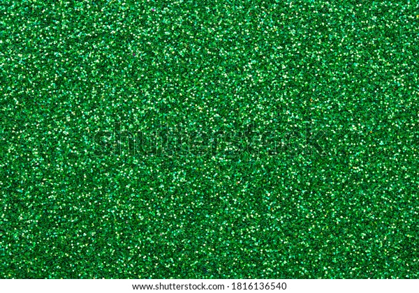 Sparkle green texture, dark glitter background. Shimmering surface of textile. Abstract glister pattern. Brilliance backdrop. Holiday design.