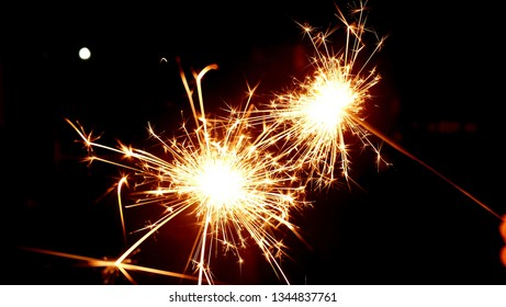 Sparkler background / A sparkler is a type of hand-held firework that burns slowly while emitting colored flames, sparks, and other effects.