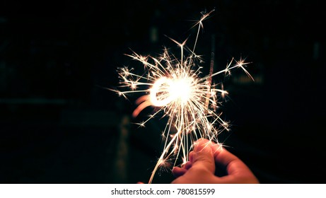 Sparkler background / A sparkler is a type of hand-held firework that burns slowly while emitting colored flames, sparks, and other effects