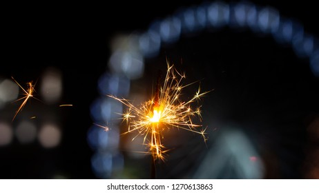 sparkler A beautiful flame on the background of the street with a sight wheel. Concept for the new year and the day of lovers.