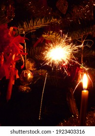 A sparkler is hanging on a Christmas tree.