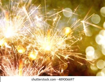 sparkler on gold bokeh background macro close up