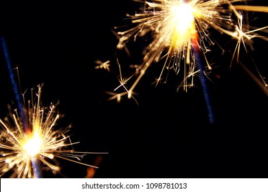 Sparklers as background / A sparkler is a type of hand-held firework that burns slowly while emitting colored flames, sparks, and other effects.