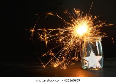 sparklers in a glass jar with a star on a wooden table