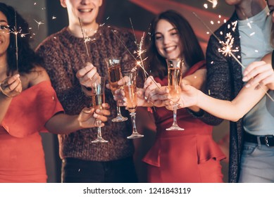 Sparkles everywhere. Multiracial friends celebrate new year and holding bengal lights and glasses with drink.
