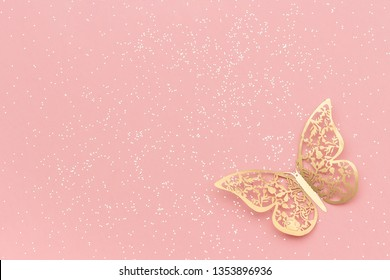 Sparkles glitter and gold tracery butterfly on pink pastel trendy background. Festive background, template.