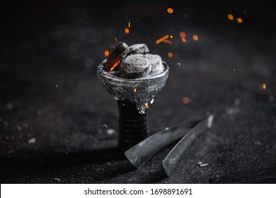 sparkles of hot coal on tha top of hookah's head or bowl. Handcrafted old, rustik, gold sheesha with glowing sparkles of hot coal. Dark background
