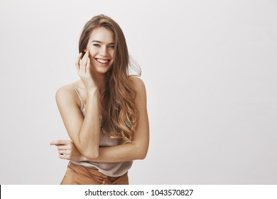 Sparkling beautiful woman. Charming sensual girlfriend standing in glamorous outfit gently touching cheek and smiling playfully, posing and gazing at camera flirty, showing interest and affection