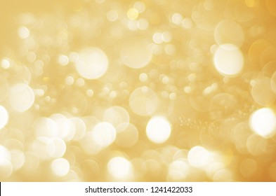 A sparkling bokeh background blur in gold and white.