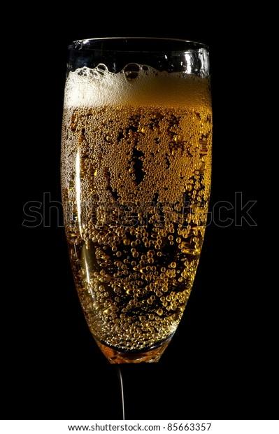 Sparkling Champagne Glass. Elegant Glass - Black Background. Vertical Photo.