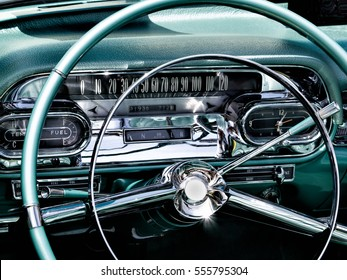 A sparkling closeup of a chrome and teal antique car dashboard with sun reflections at a car show in Mizner Park, Boca Raton FL