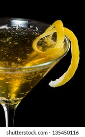 sparkling cocktail decorated with a long lemon twist isolated on a black background