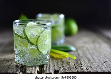 Sparkling cold water detox with lime and ice on a dark wooden background old