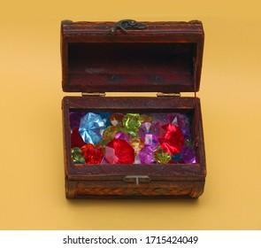 Sparkling colorful diamonds pile inside vintage wooden chest