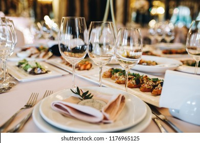 Sparkling crystal glasses stand on rich served dinner table