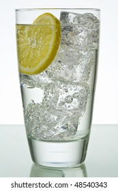 Sparkling drink in glass with ice cubes and lemon slice