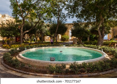 Sparkling fountain under peaceful trees and limestone arches on the background, Upper Barrakka Gardens park, Capital city of Malta, Valletta.